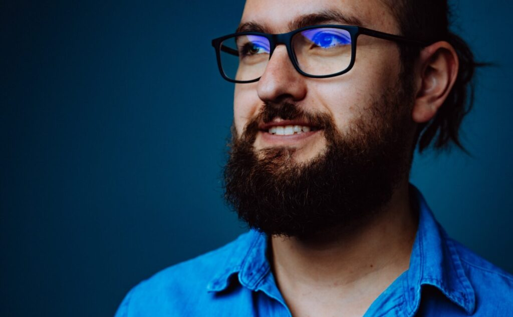 new HR hire man in blue with glasses smiling