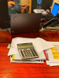 Calculator on red desk to determine cost to terminate an employee
