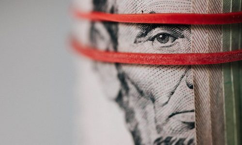 Dollar bill wrapped with red rubber band