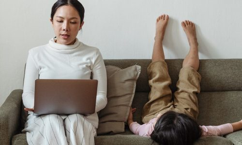 Mother working from home remote work with child on couch