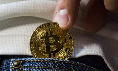 fingers putting bitcoin into jeans pocket